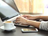 Tippen am Laptop, daneben eine Tasse Kaffee und ein Smartphone