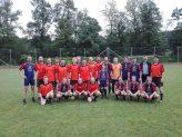 Die zwei Fußball-Teams posieren für ein Foto auf dem Spielfeld