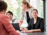 Eine in die Kamera lächelnde Frau vor einem Laptop, die mit anderen Menschen an einem Tisch sitzt.