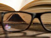 Eine Brille liegt vor einem Buch.