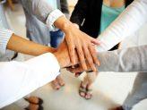 Mehrer Hände treffen sich in der Mitte des Bildes.