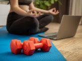 eine Frau sitzt auf einer Yogamatte vor ihrem Laptop