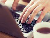 eine Kaffeetasse steht neben einem Laptop